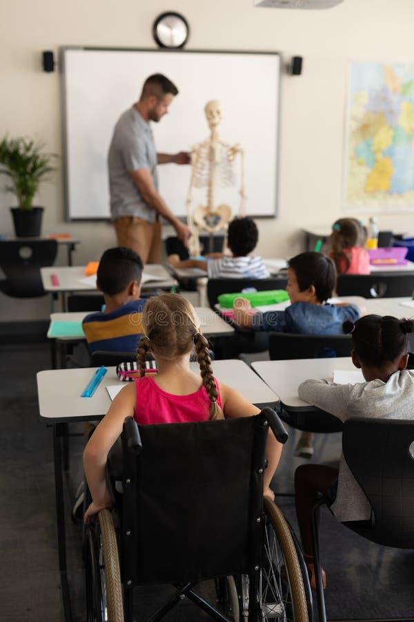 Школьница отключения с одноклассником изучая в классе сидя на столе начальной школы стоковое фото