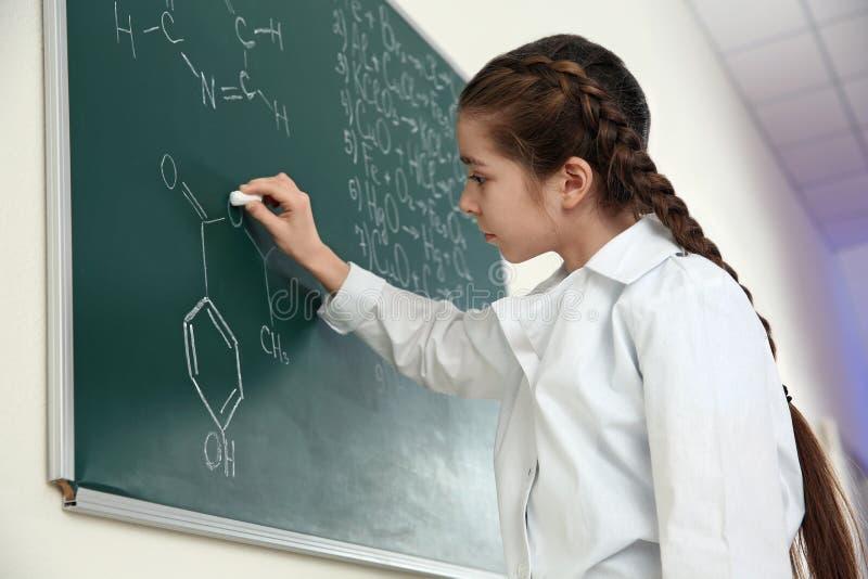 Школьница писать формулу химии на классн классном стоковая фотография rf