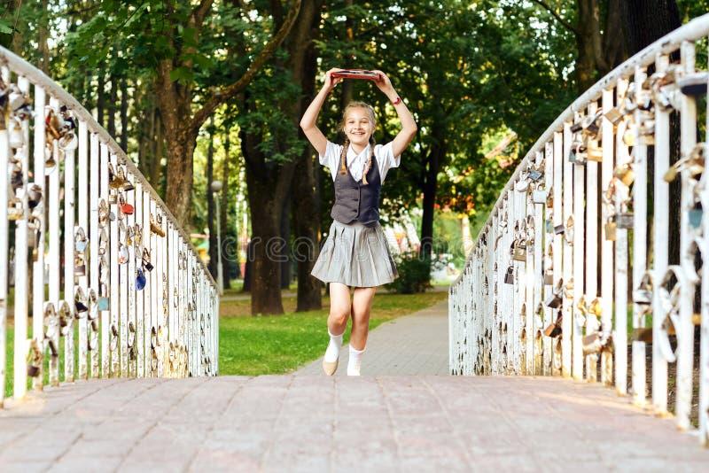 Школьница студента счастливая с отрезками провода в форме с книгами в руках над главным brid бегов сверх стоковое фото