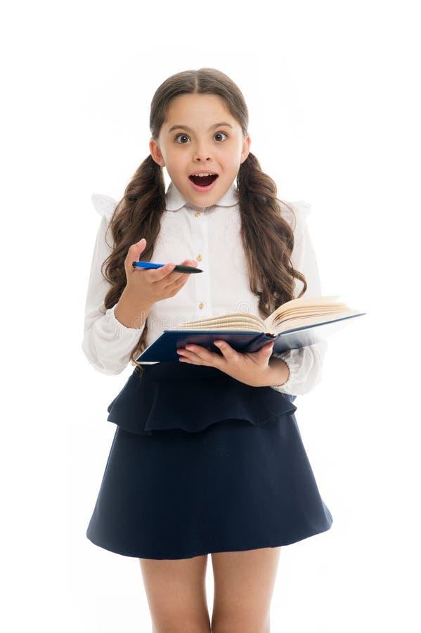 Школьница с удивленным взглядом изолированная на белизне Книга владением маленького ребенка с ручкой задняя школа к Домашнее обуч стоковые изображения rf