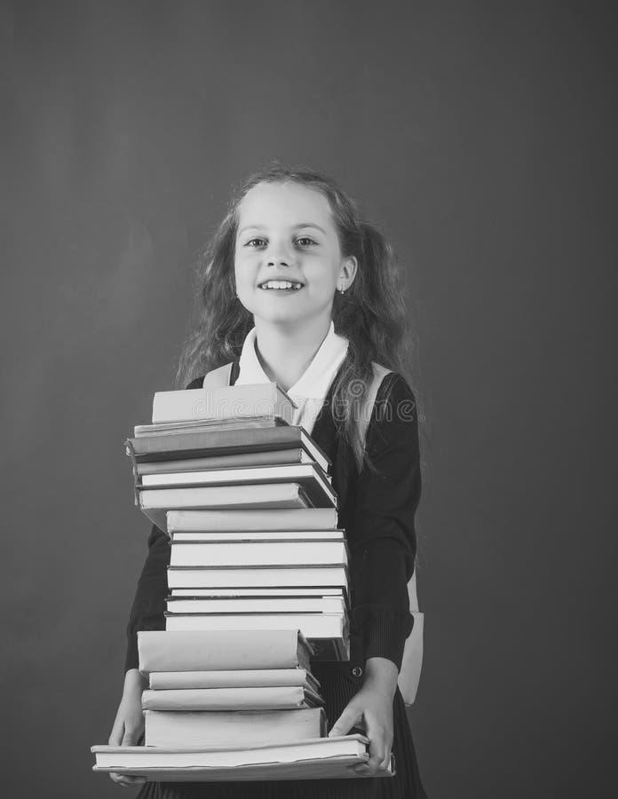Школьница с усмехаясь стороной держит огромную кучу книг стоковое фото