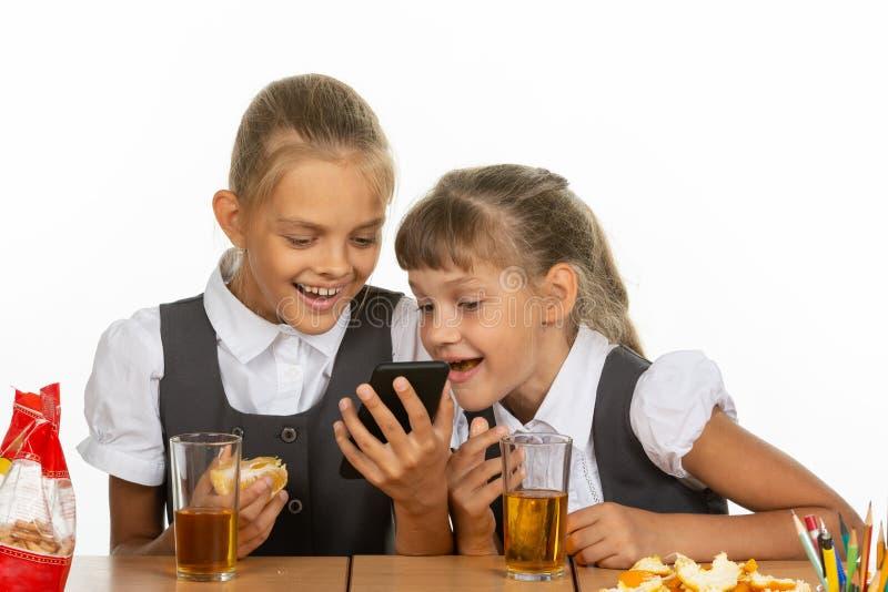 2 школьницы на перерыве наблюдая видео по телефону, и есть печень и апельсин, выпивая сок стоковые фотографии rf