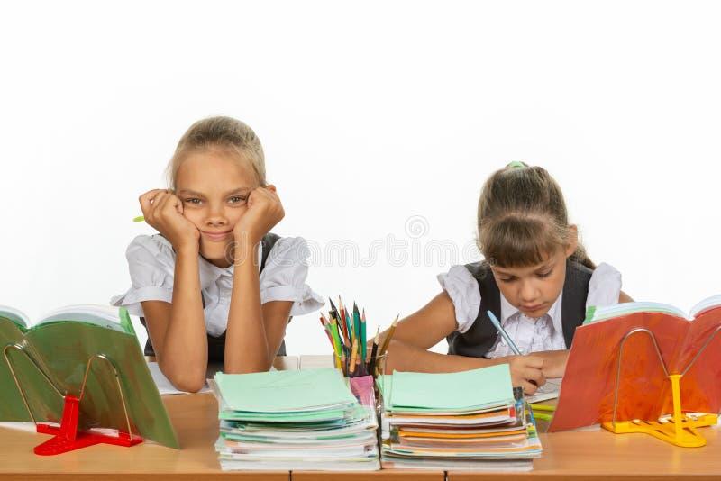 2 школьницы на столе, одной склонности на ее руках и смотреть в рамку, другое пишут стоковые фотографии rf