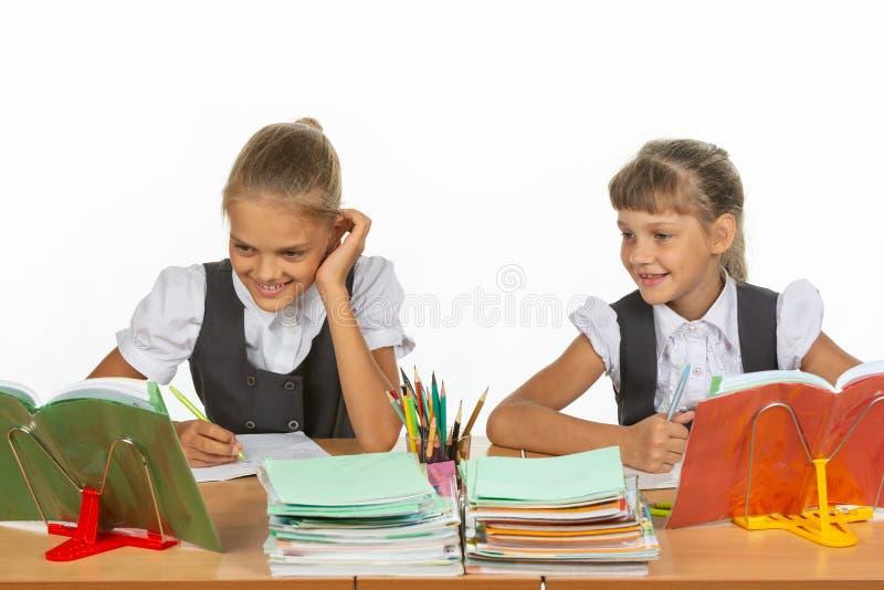 2 школьницы сидят на столе и жизнерадостно смотрят учебник стоковая фотография