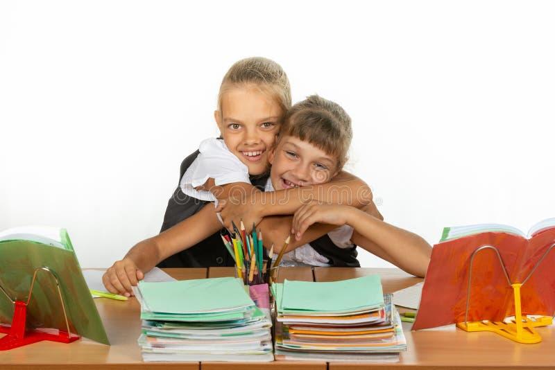2 школьницы сидят на столе смотря учебники стоковые изображения