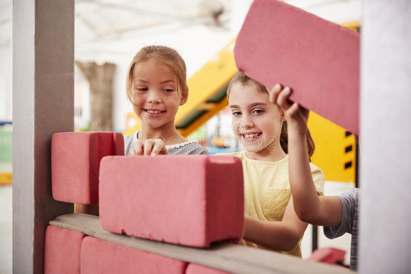 Школьницы строя с кирпичами игрушки, концом вверх стоковое фото rf