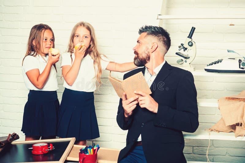 Школьное время сестер и отца в библиотеке Книга грамматики урока и чтения литературы Образование во дне знания стоковое изображение