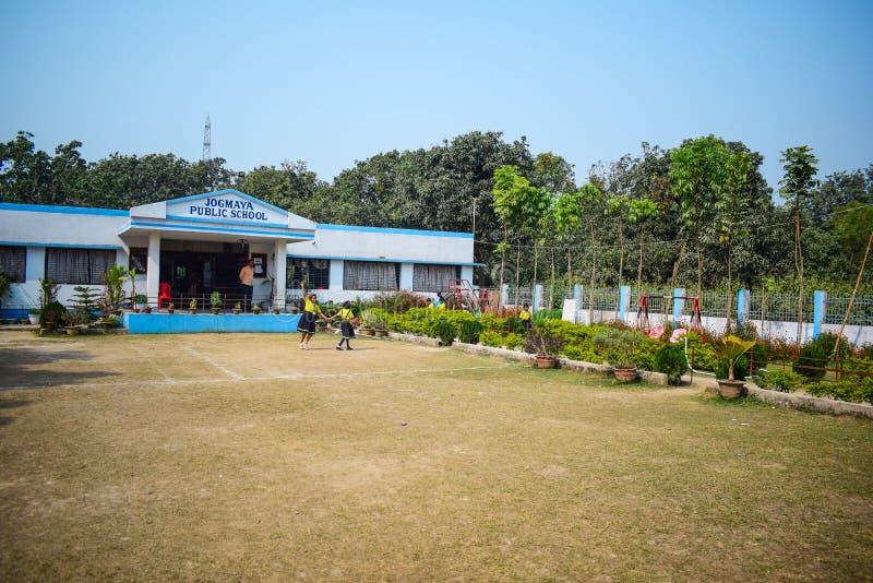 Школьное здание детского сада со спортивной площадкой перед ей стоковое изображение