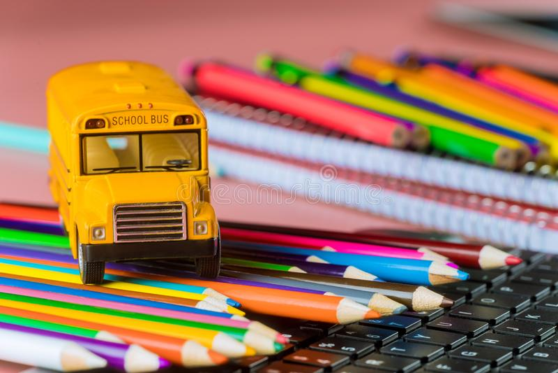 Школьный автобус на карандашах цвета и клавиатуре, задней части в школу стоковое изображение
