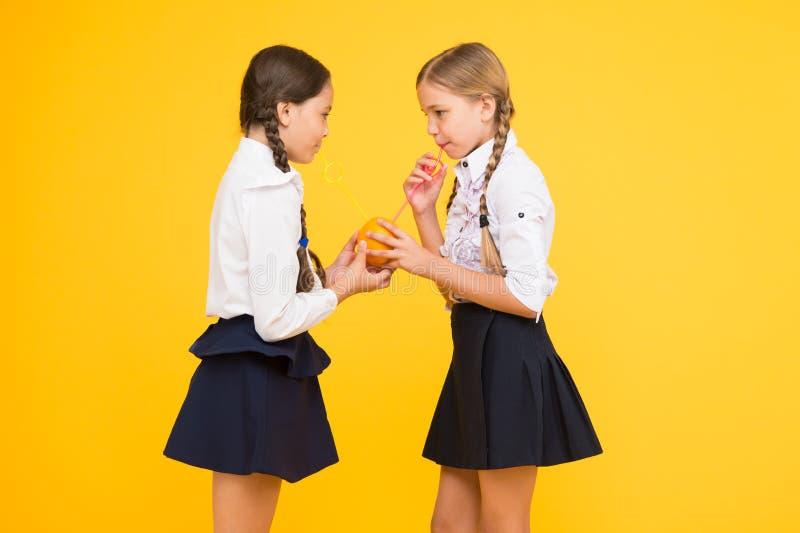 Школьный обед Питание витамина Школа свежих фруктов Школьная форма детей девушек выпивая сок оранжевого плода свежий стоковые фотографии rf