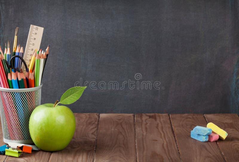 Школа и канцелярские товары на таблице класса стоковые изображения
