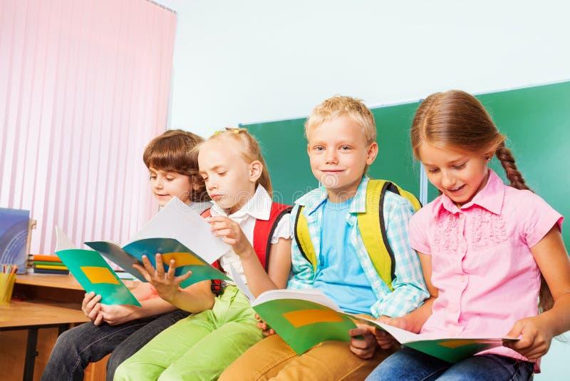 4 школьника сидят в строке на столе и читают стоковое фото rf