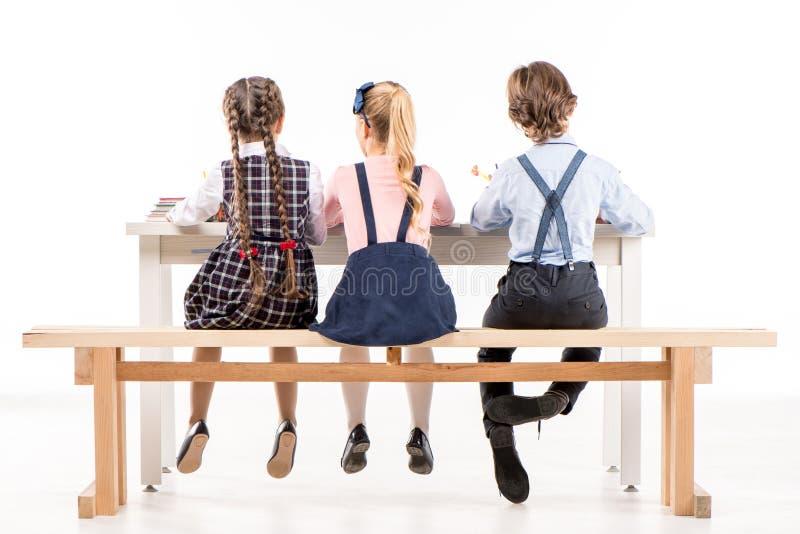 Школьники изучая на столе стоковое изображение rf