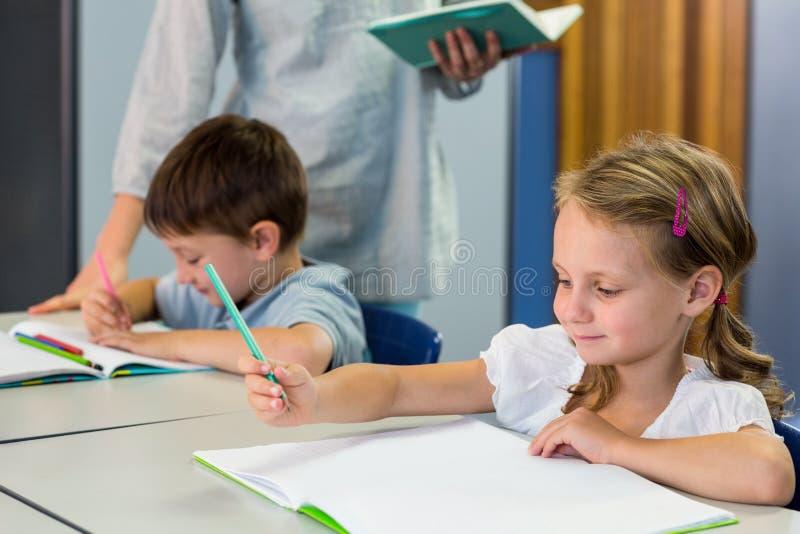 Школьники писать на книге против учителя стоковое фото