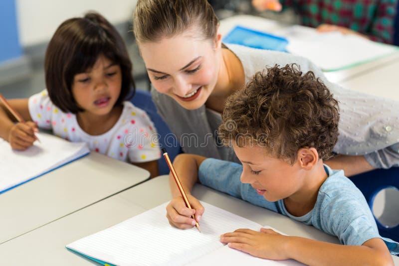 школьники порции учителя, который нужно написать на книге стоковое изображение