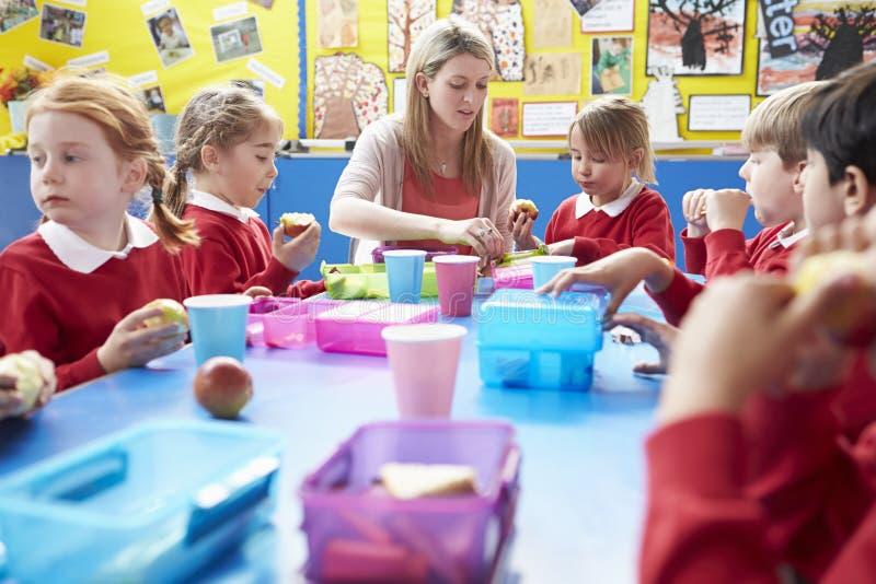 Школьники при учитель сидя на таблице есть обед стоковое фото