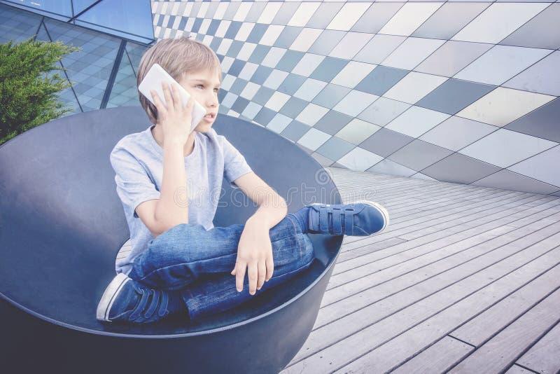 Школьник говоря на телефоне в городе стоковая фотография
