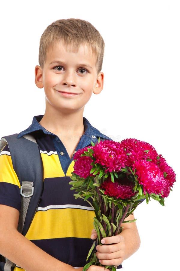 Школьник держит цветки задняя школа к стоковое фото