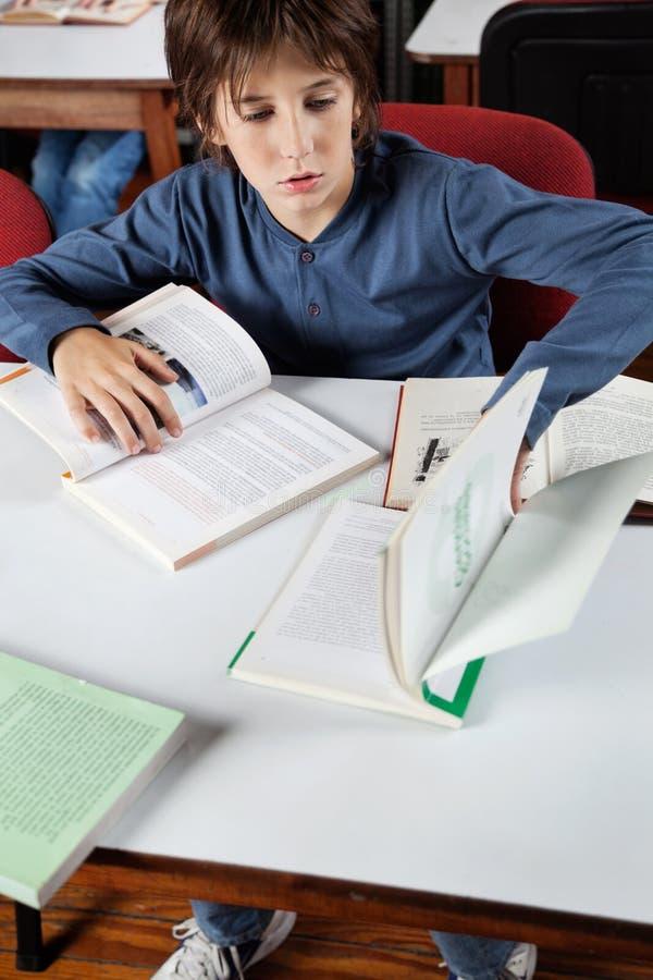 Школьник изучая в библиотеке стоковое фото rf