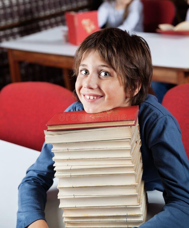 Школьник отдыхая Chin на штабелированных книгах на таблице стоковая фотография rf