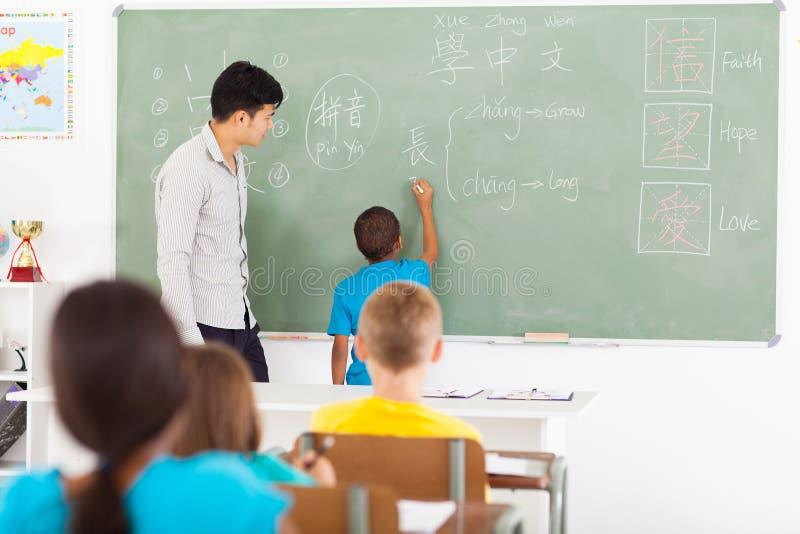 Школьник писать китайцу стоковые изображения
