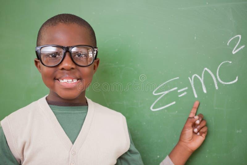 Школьник показывая массоэнергетическую equivalence формулу стоковые фото