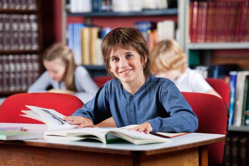 Школьник усмехаясь с книгами на таблице в библиотеке стоковые изображения
