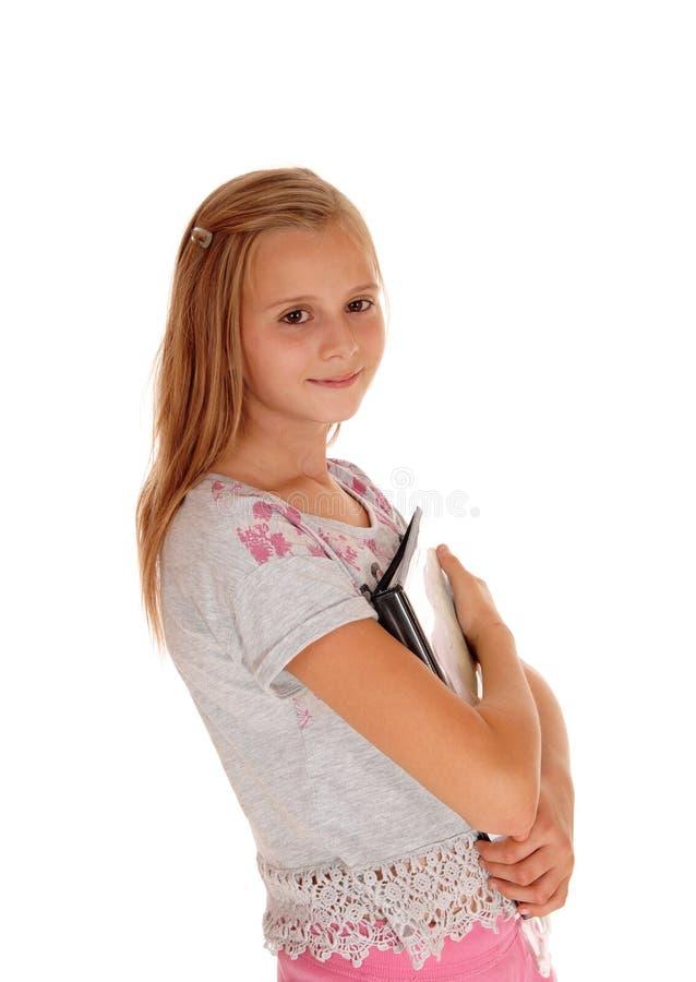 Школьница держа ее книги к ее комоду стоковое фото