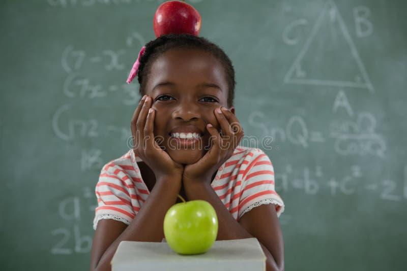 Школьница сидя с красным яблоком на ее голове против доски стоковое изображение rf