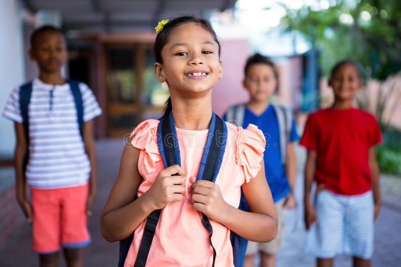Школьница с одноклассниками на коридоре школы стоковые фотографии rf