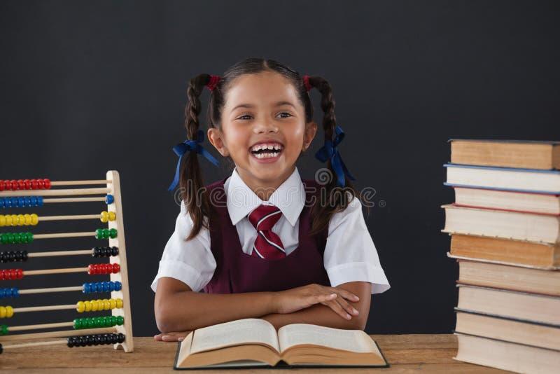 Школьница читая книгу против доски стоковая фотография