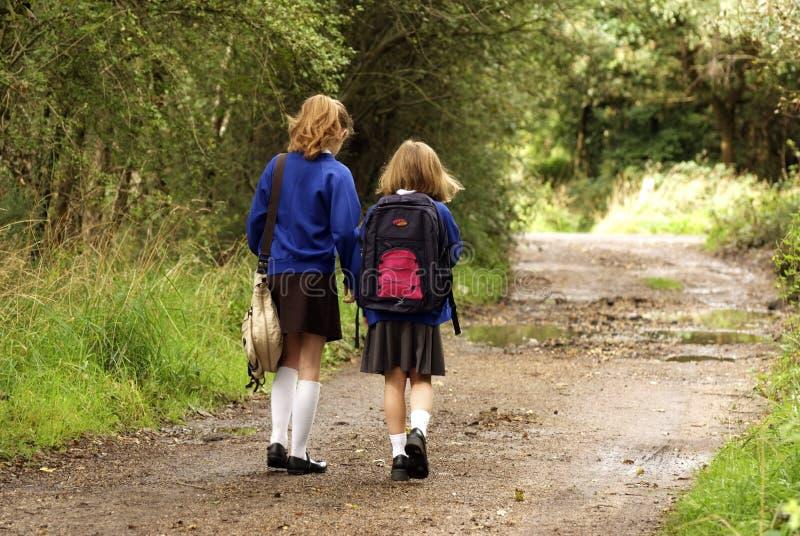 Школьницы в форме идя к школе стоковая фотография rf
