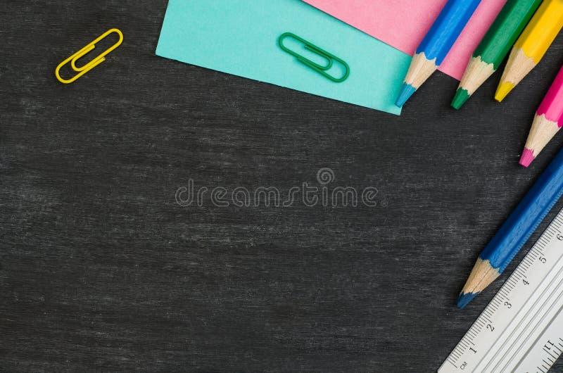 Школьные принадлежности граничат на черной предпосылке доски Фотоснимок взгляд сверху стоковая фотография