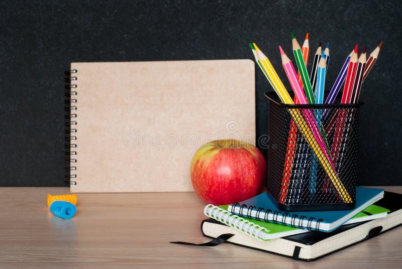 Школьные принадлежности на таблице класса стоковые изображения rf
