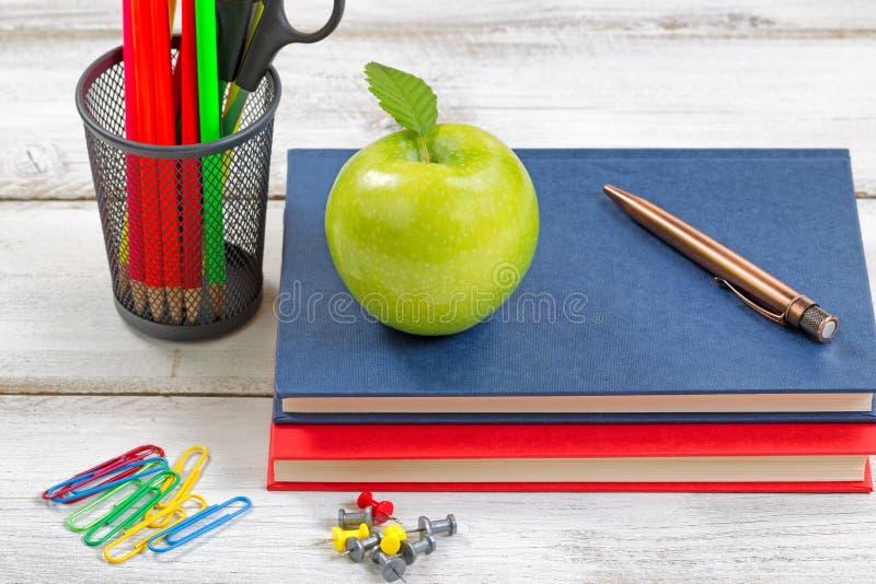 Школьные принадлежности с учебниками на белом настольном компьютере стоковое изображение