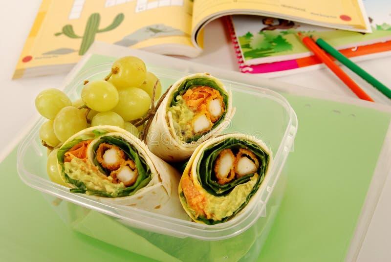 Школьный обед: сандвич обруча цыпленка в пластичной коробке с книгами на столе школы стоковые изображения rf
