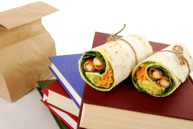Школьный обед: сандвич обруча цыпленка с сумкой обеда, книгами на столе школы стоковое фото rf