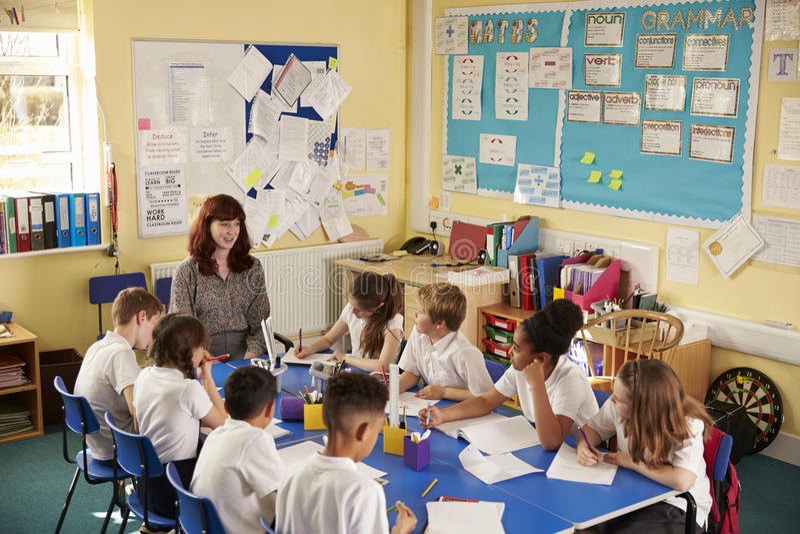 Школьный учитель и дети работают на проекте класса, повышенном взгляде стоковая фотография