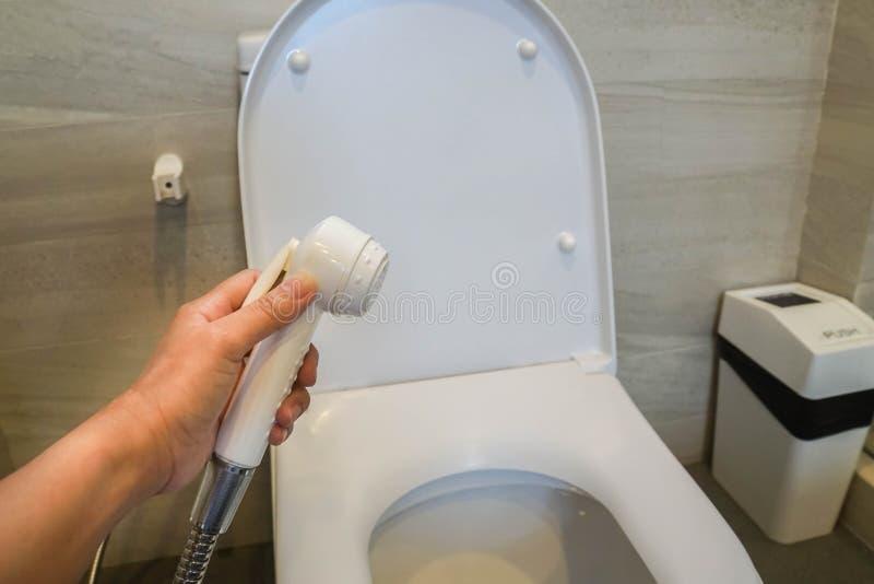 Шланг брызга rinse владением женщины в туалете для очищать стоковое изображение rf