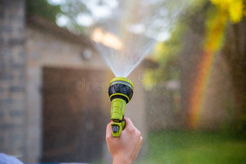 Шланг сада удерживания руки женщины и распыляя вода для создания радуги Радуга на заднем плане создалась мягким туманом от сада стоковая фотография