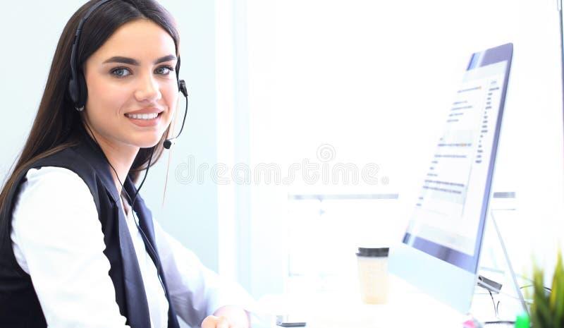 Шлемофон микрофона коммерсантки нося используя компьютер в офисе - оператора, центр телефонного обслуживания стоковые изображения