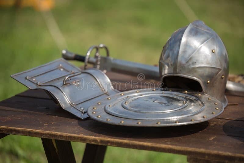 Шлемы, экраны и средневековые металлические панцыри и оружия, Outdoors на деревянном столе стоковое изображение
