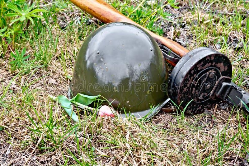 Шлем и пистолет-пулемет с тюльпаном на траве стоковые фото