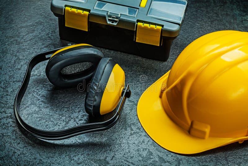 Шлем и резцовая коробка наушников на черной предпосылке стоковое изображение