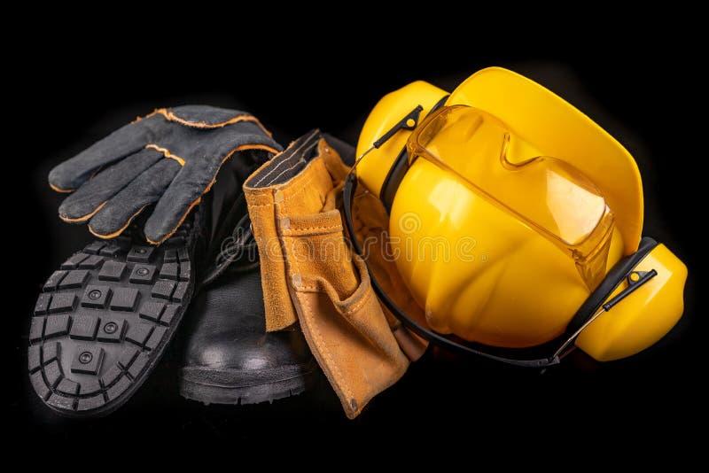 Шлем, перчатки и ветроуловитель на темном верстаке Аксессуары безопасности и гигиены для рабочий-строителей стоковое изображение