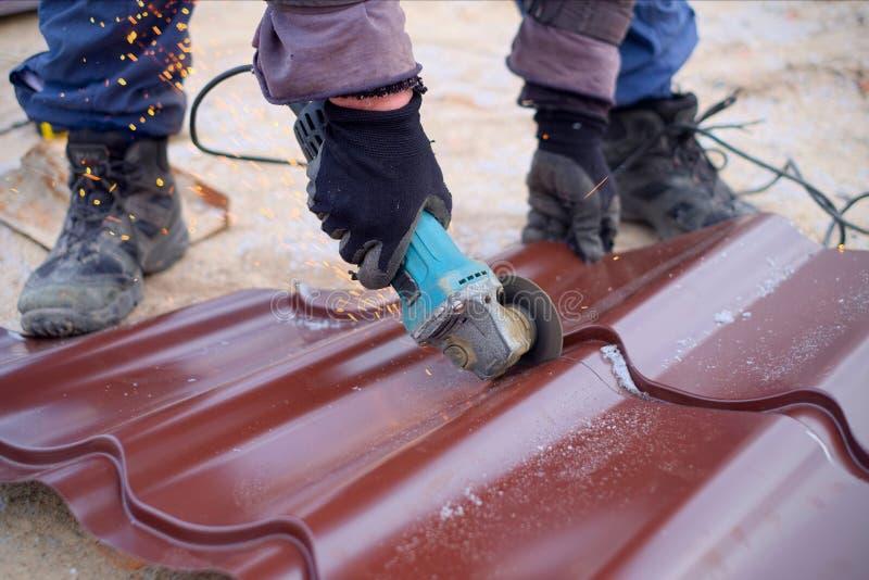 Шлифовальный станок пользы работника для листов крыши инструментального металла Roofer использует электрический инструмент строя  стоковое фото