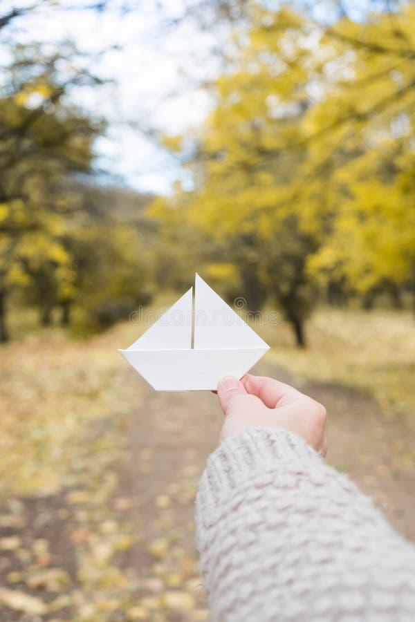 Шлюпка белой бумаги в руке в парке осени стоковая фотография