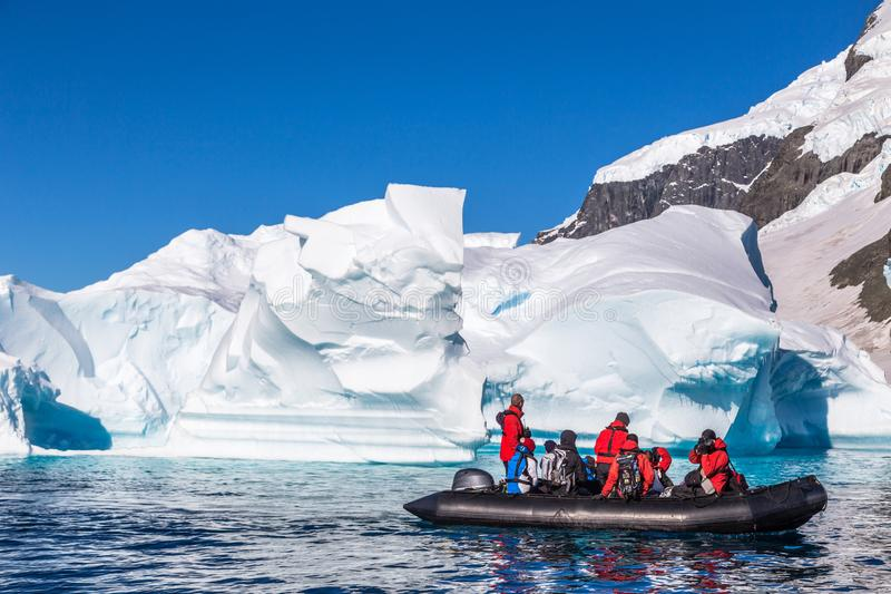 Шлюпка вполне туристов исследует огромные айсберги перемещаясь в залив стоковое изображение rf
