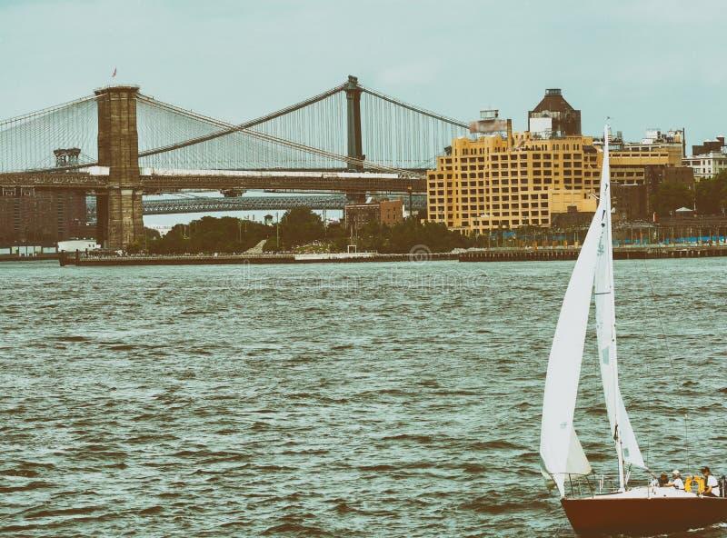 Шлюпка в Нью-Йорке с мостом Бруклина и Манхаттана в backgroun стоковые фотографии rf