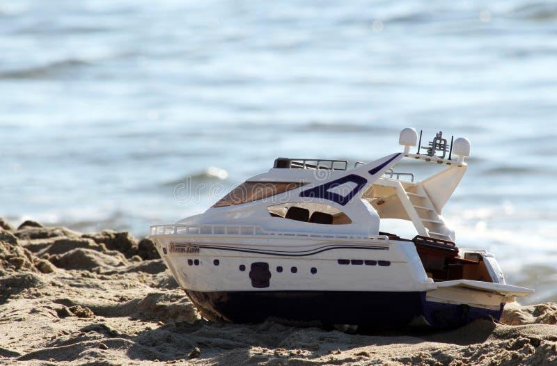 Шлюпка игрушки на пляже стоковые фотографии rf